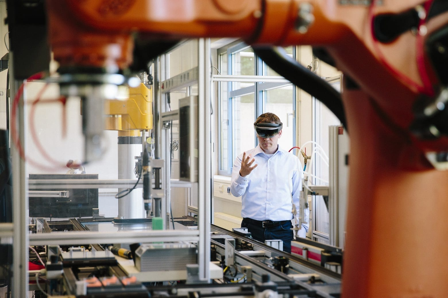 engineer works with a HoloLens: place a virtual robotic arm into the production line