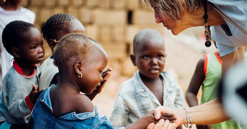Humanitarian worker from NGO greeting children in Africa