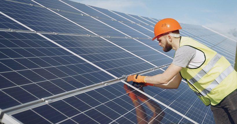 a technician installing solar panel in solar farm